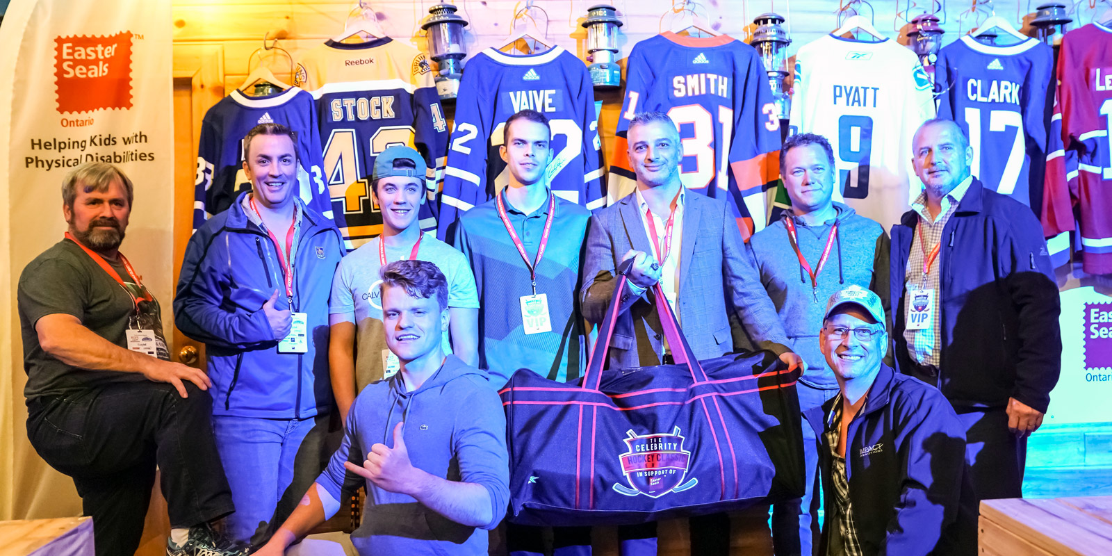 members of the 2019 Thunder Bay $1500 club pose holding up the crested hockey bag